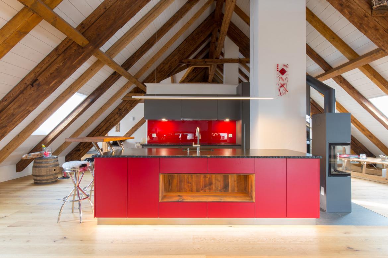 rote Küche in ausgebautem Bauernhaus