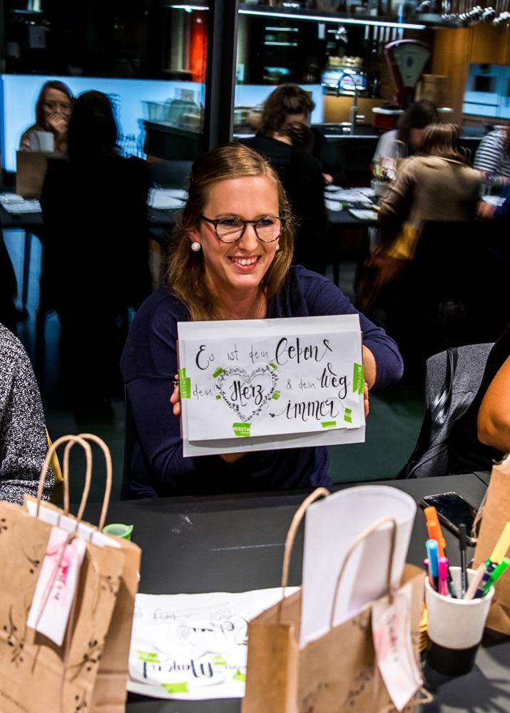 Eine Teilnehmerin des Handlettering-Kurses mit Ruth Kühni zeigt ihren Entwurf.